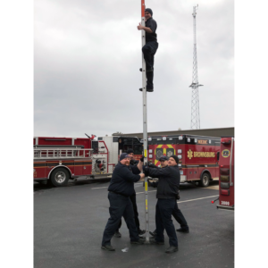 Firefighters holding up a 20 foot ladder vertically while another firefighter poses at the top of the ladder